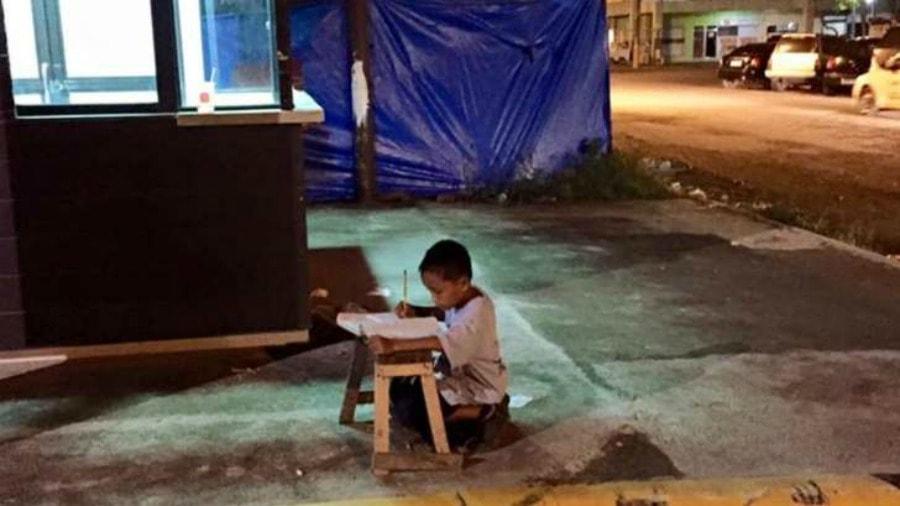 Homeless little boy studying under light of McDonalds